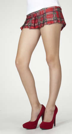 mini falda: Primer plano de las piernas de mujer s en una escuela de la muchacha plaid mini falda y tacones rojos