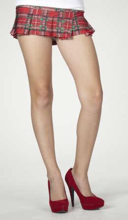minifalda: Primer plano de las piernas de mujer s en una escuela de la muchacha plaid mini falda y tacones rojos
