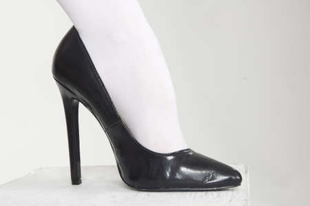 dominance: Close up of woman s high heel shoes against a white studio background