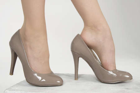 putting up: Close up of woman s high heel shoes against a white studio background
