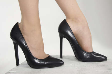 Close up of woman s high heel shoes against a white studio background