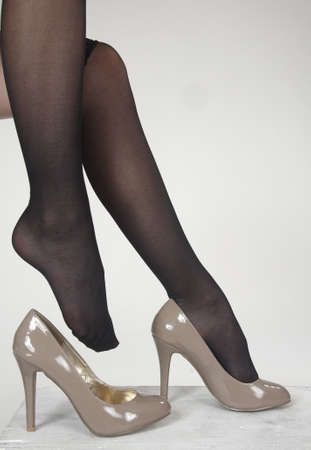 stocking feet: Close up of woman s high heel shoes against a white studio background
