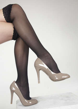 stockings feet: Close up of woman s legs crossed wearing high heels Stock Photo