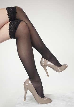 tacones negros: Cerca de las piernas de la mujer s cruzaron usar tacones altos