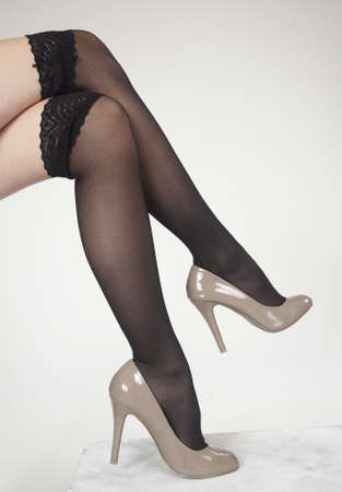putting up: Close up of woman s legs crossed wearing high heels Stock Photo