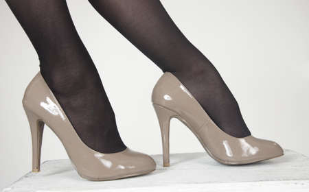 women s feet: Close up of woman s high heel shoes against a white studio background