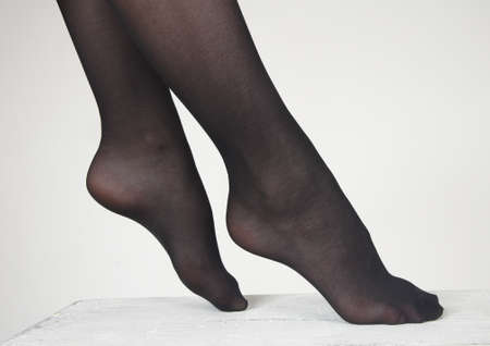 women s legs: Close Up of woman s feet wearing dark sheer pantyhose against a white studio background