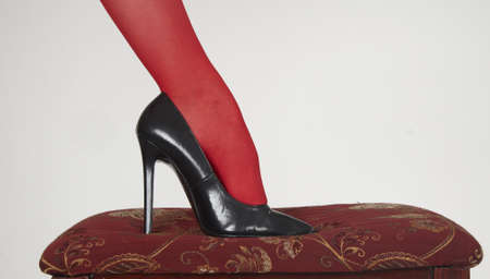 stepping: Close up of woman s high heels on a classic red bench