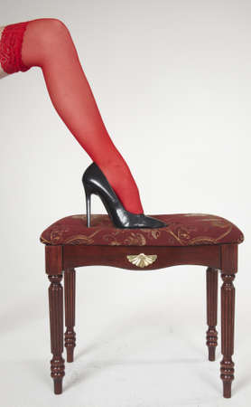 stockings heels: Close up of woman s high heels on a classic red bench