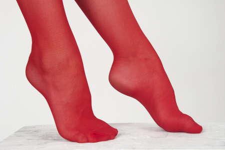 Close-up van een vrouw s voet dragen van rode panty tegen een witte achtergrond studio