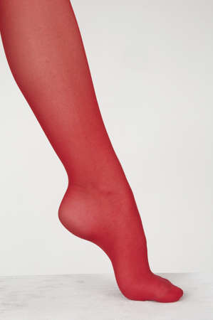 women s legs: Close Up of woman s foot wearing red sheer pantyhose against a white studio background