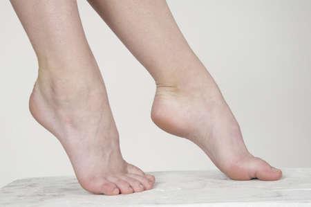 pies sexis: Cerca de la mujer s pies desnudos sobre un fondo blanco de estudio Foto de archivo