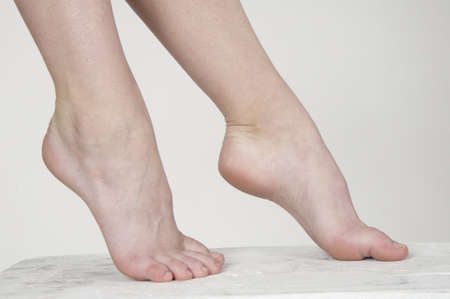 foot fetish: Close up of woman s bare feet against a white studio background