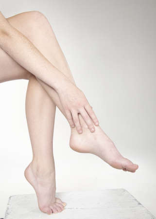 calves: woman s bare legs crossed against a white studio background