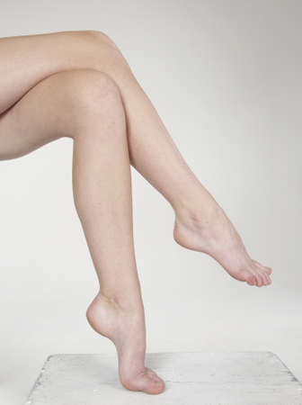 ankles sexy: Close-up of woman s bare legs crossed against a white studio background Stock Photo