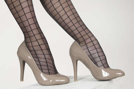 women s feet: Close up of woman s high heel shoes and striped pantyhose against a white studio background