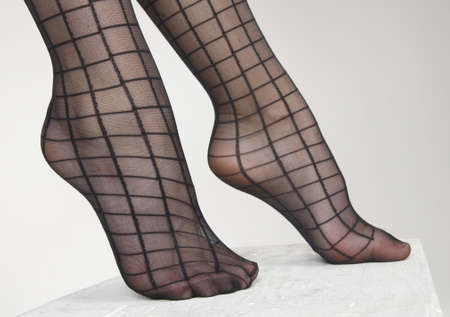 ankles sexy: Close Up of woman s feet wearing dark sheer striped pantyhose against a white studio background