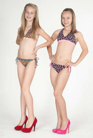 pre teens: Two teen girls posing in bikinis and heels against a white studio background