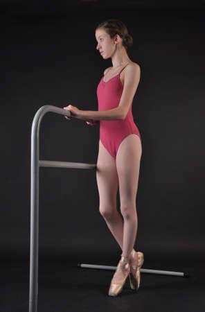 leotard: Ballerina Posing En Pointe Next to a Ballet Bar