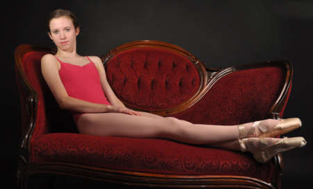 white sofa: Ballet Dancer Relaxing on Couch Stock Photo