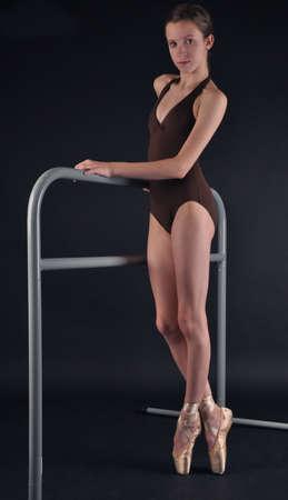 Ballerina Posing En Pointe Next to a Ballet Bar