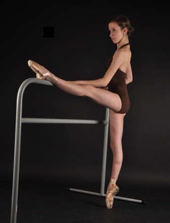 ballet bar: Ballerina Posing En Pointe Next to a Ballet Bar