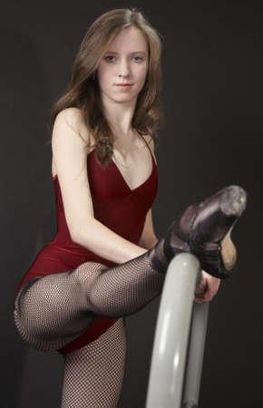 barre: Ballerina Dancer Stretching her Legs on a Ballet Bar Stock Photo