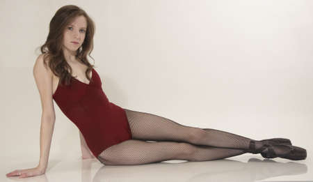 Ballerina Posing in a Red Leotard and Black Fishnet Tights and Shoes photo