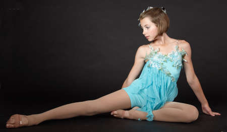 Young Girl Ballerina Posing Against a Black Studio Background photo
