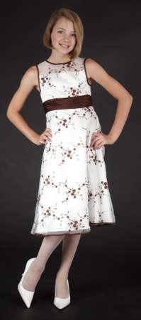 十代の少女のドレスと黒のスタジオの背景に対してハイヒールでポーズ 写真素材