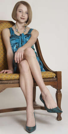 formal attire: Pretty Teen Girl in a Short Skirt and Heels Sitting with her legs crossed Stock Photo