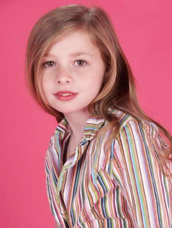 Blond Teen Girl Portrait Against a Pink Studio Background photo