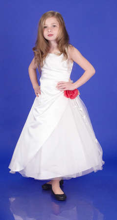 Preteen Blond Girl in a White Formal Dress and Heels Against a Blue Background photo