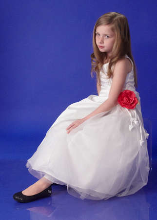 Preteen Blond Girl in a White Formal Dress and Heels Against a Blue Background