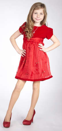 赤いドレスを着てのプレティーンのブロンドの女の子