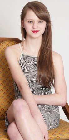 leggy: Teen Girl Sitting in a Grey Dress Stock Photo