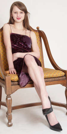 crossed legs: Teen Girl Sitting in a Skirt and Heels Stock Photo