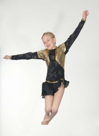 Teen blond girl jumping for joy in theatrical costume photo