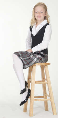 tights: Private School Girl Posing on a Stool in Uniform with White Socks Stock Photo