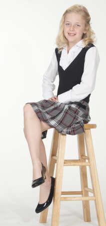 Catholic School Girl Posing on a Stool in Uniform photo