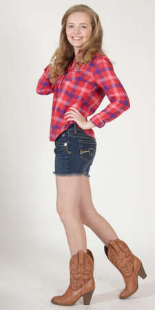 western attire: Blond teen girl in cowgirl boots, jean shorts and western style shirt