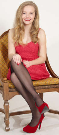 Portrait of a blond teen girl in an elegant red dress