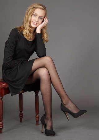 Blond Teen Girl in a Black Dress, Stockings, and Heels Against a Black Studio