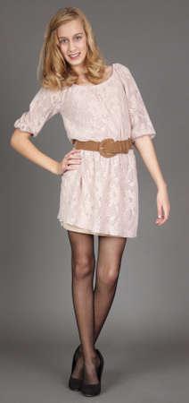 팬티 스타킹: 탄 드레스, 스타킹, 검은 스튜디오 배경에 대해 발 뒤꿈치에 금발 하이틴 소녀