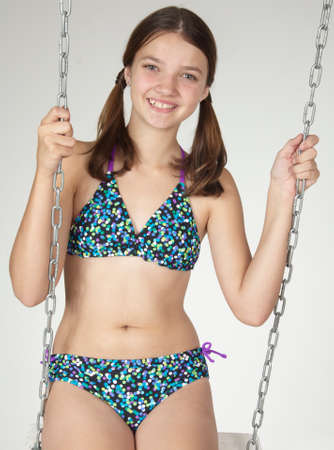 two piece bathing suit: Teen Girl in a Bikini on a Swing Against a White Studio Background Stock Photo