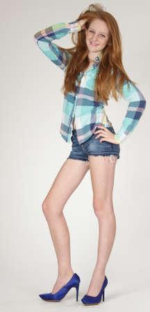 Rood Hoofd Tiener in korte broek en hoge hakken Stockfoto