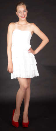 the girl in stockings:  Blond Girl in White Dress and Heels Against a Black Background