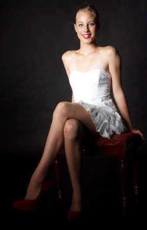 pantimedias: Chica rubia en vestido blanco y tacones contra un fondo Negro Foto de archivo