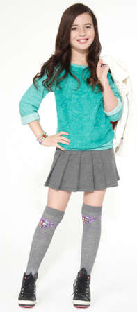 Presentación modelo adolescente en una falda gris y calcetines largos contra un fondo de estudio