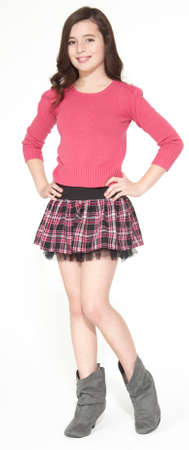 pre teen girls: Teen model posing in a plaid school skirt and ankle boots and pink sweate Stock Photo